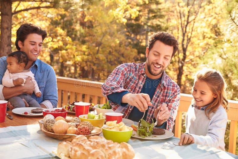 吃快乐男性的夫妇与女儿的室外午餐 免版税图库摄影