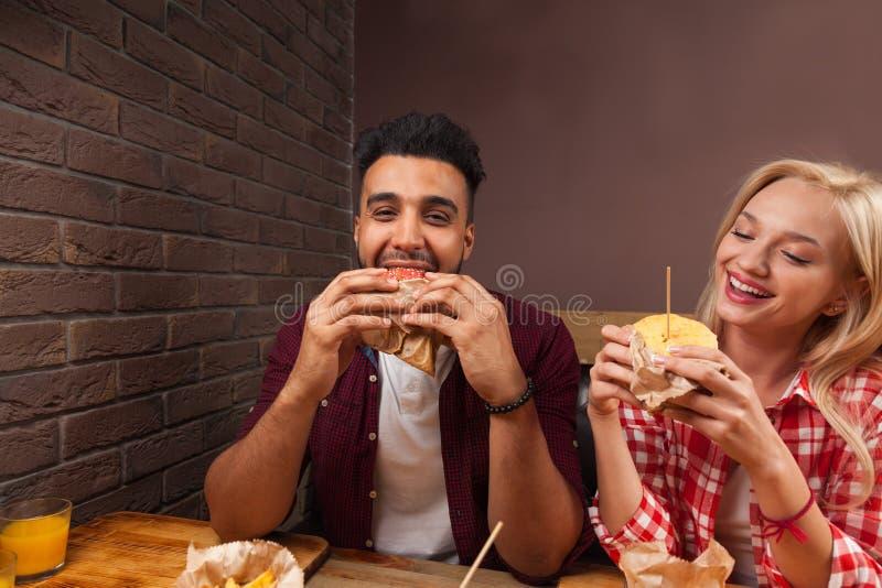 年轻吃快餐汉堡的人和妇女坐在咖啡馆的木表上 免版税库存图片