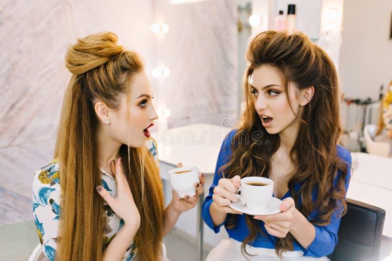 吃惊的两使可爱的妇女惊奇谈话在发廊 饮用的咖啡,准备集会,获得乐趣 图库摄影