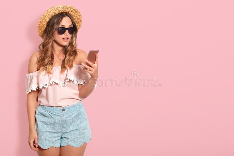 吃惊的俏丽的妇女佩带的女衬衫,短小,草帽和太阳镜画象有露出的肩膀的,拿着智能手机与 免版税库存图片