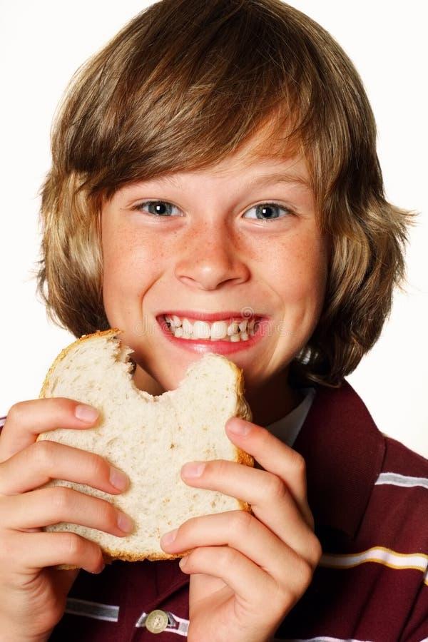 吃愉快的三明治的男孩 库存照片