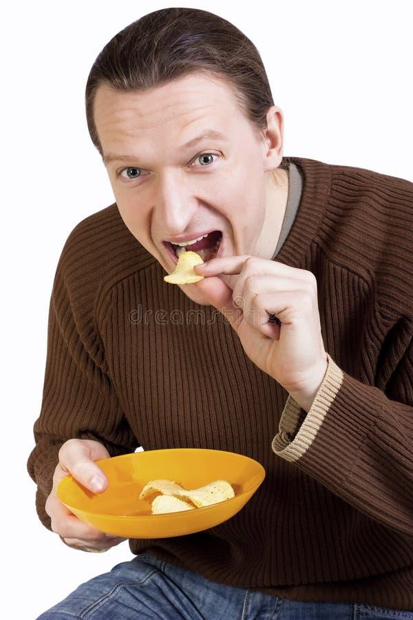 吃愉快的人土豆年轻人的筹码 免版税库存照片