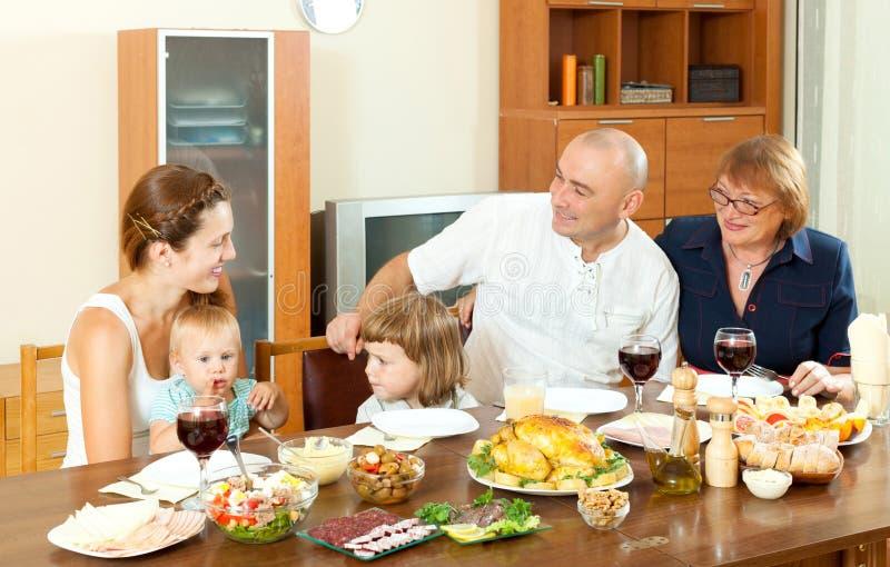 吃愉快的多代的家庭假日晚餐 免版税库存图片