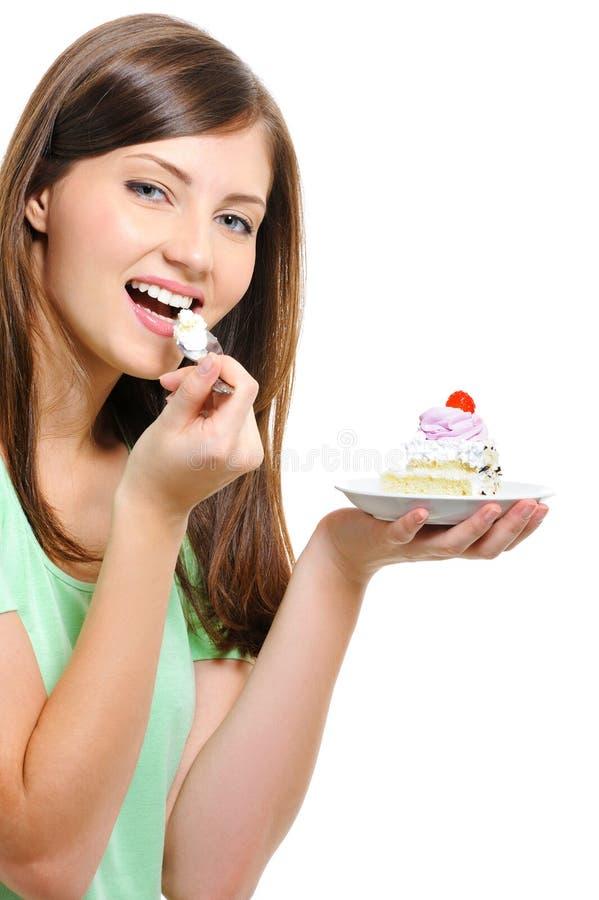 吃愉快的妇女年轻人的美丽的蛋糕 图库摄影