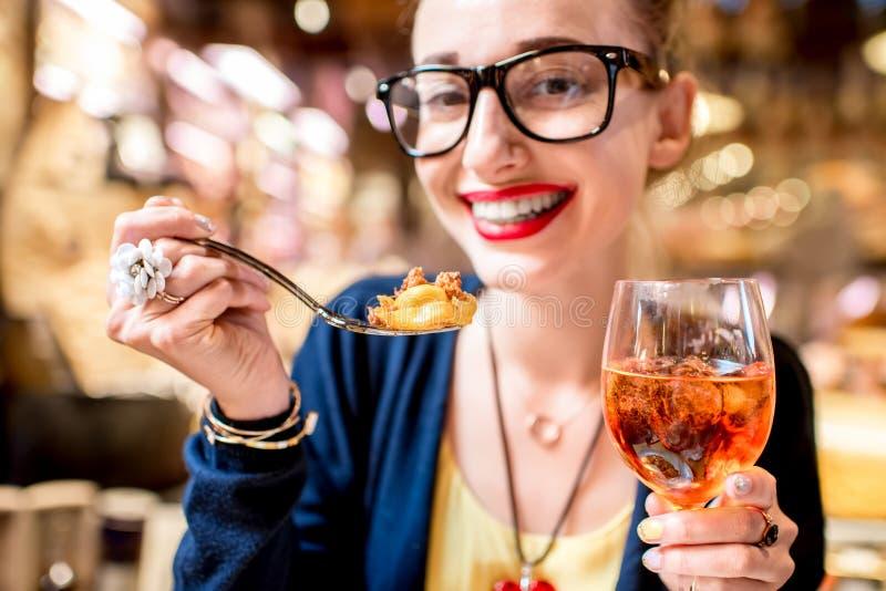 吃意大利式饺子面团的妇女 库存图片