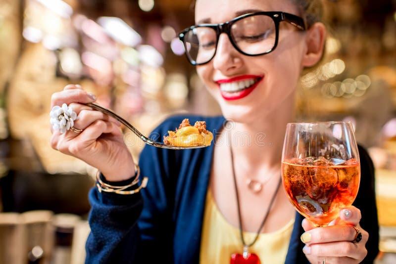 吃意大利式饺子面团的妇女 免版税库存图片