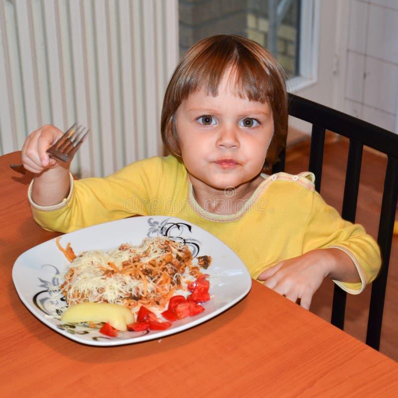吃意粉的逗人喜爱的矮小的棕色头发女孩 免版税库存图片