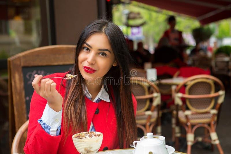 吃提拉米苏沙漠的妇女在意大利餐馆 免版税库存图片