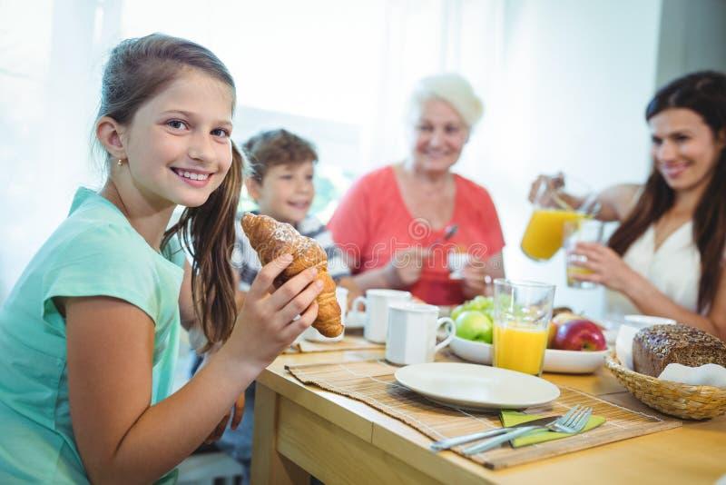 吃新月形面包的微笑的女孩,当食用早餐时 图库摄影
