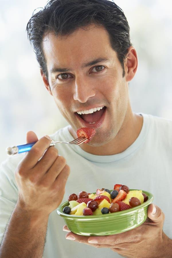吃新鲜水果人中间沙拉的成人 免版税库存照片