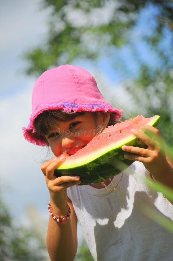 吃新鲜的女孩片式西瓜 库存照片
