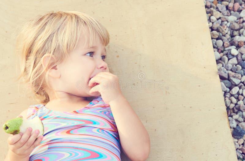 吃新鲜的梨的逗人喜爱的可爱的小孩女孩说谎在海滩 免版税库存图片