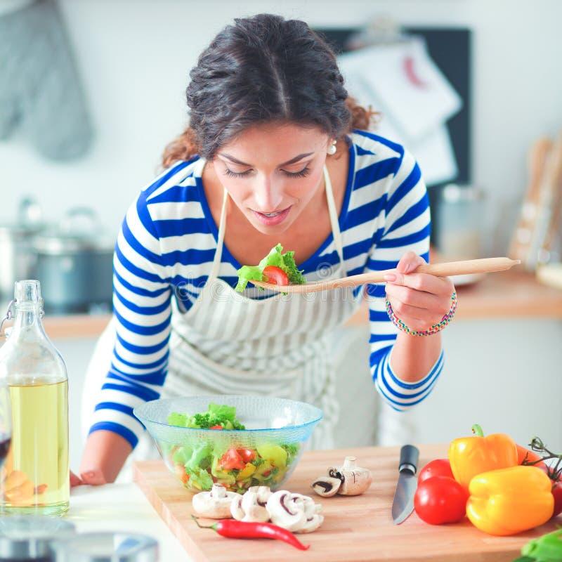 吃新鲜的沙拉的少妇在现代厨房里 免版税库存照片