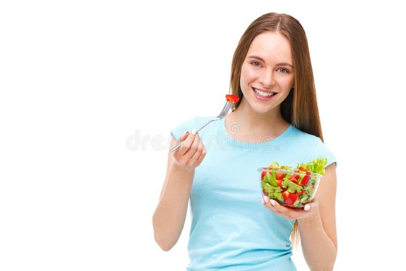 吃新鲜的沙拉的适合健康妇女的画象被隔绝 免版税库存照片