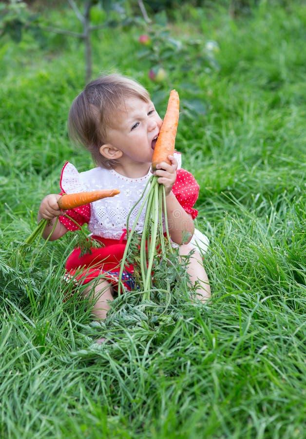 吃新鲜的红萝卜的女孩 免版税库存图片