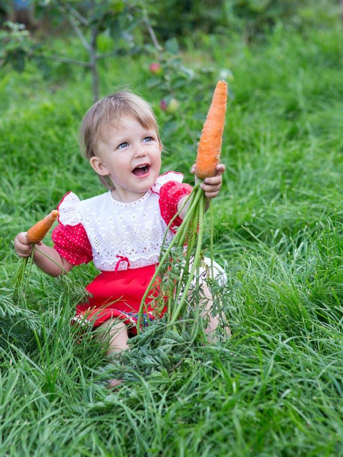 吃新鲜的红萝卜的女孩 库存照片