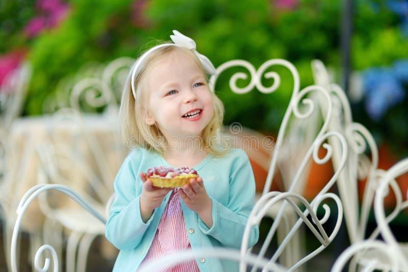 吃新鲜的草莓蛋糕的可爱的小女孩 免版税库存照片
