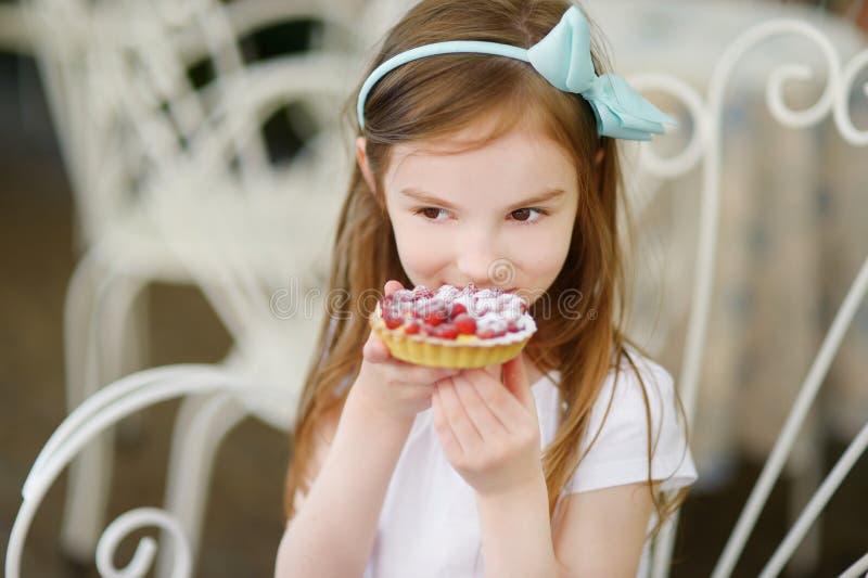 吃新鲜的草莓蛋糕的可爱的小女孩 库存图片