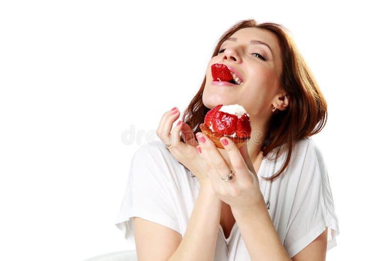 吃新鲜的草莓蛋糕的迷人的妇女 库存图片
