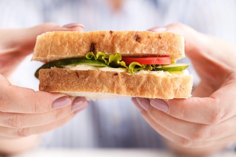 吃早餐三明治和喝咖啡的妇女,当工作时 免版税库存图片