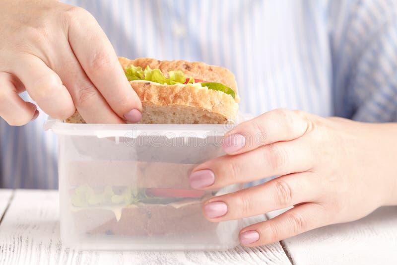 吃早餐三明治和喝咖啡的妇女,当工作时 免版税库存照片