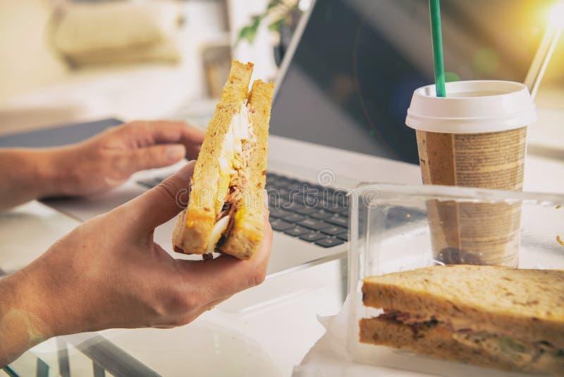 吃早餐三明治的妇女,当与膝上型计算机一起使用时 库存图片