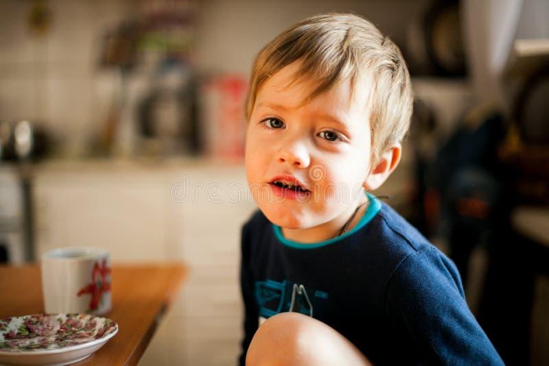 吃早餐和微笑的男孩 免版税库存图片