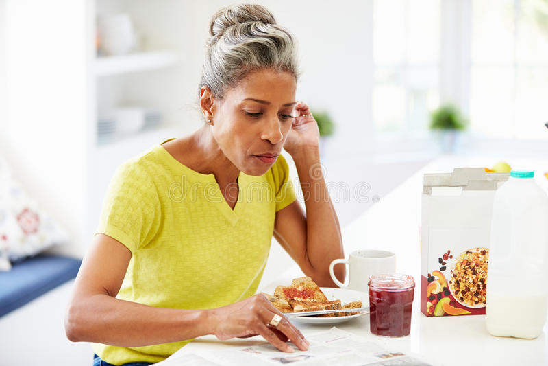 吃早餐和读报纸的成熟妇女 免版税图库摄影