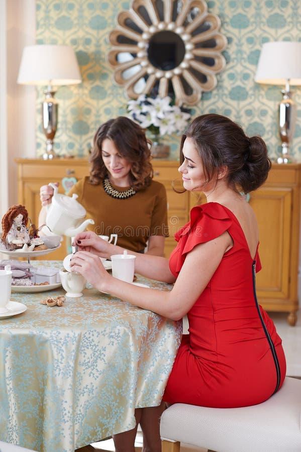 吃早餐的两个少妇在厨房用桌上 免版税库存照片