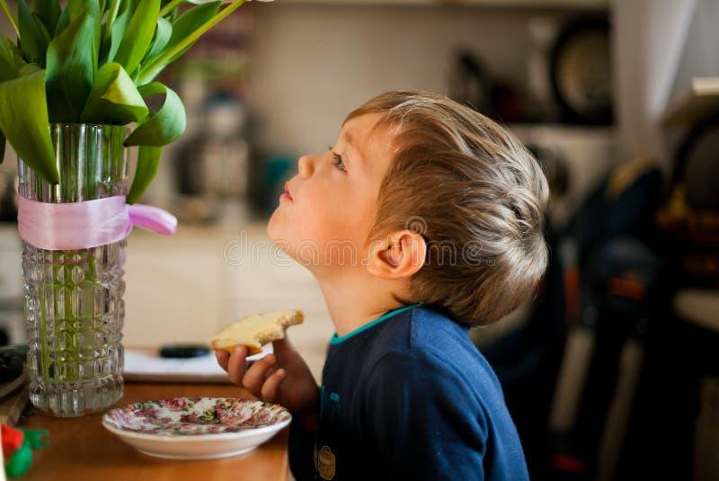 吃早餐的男孩的画象在桌上 库存照片