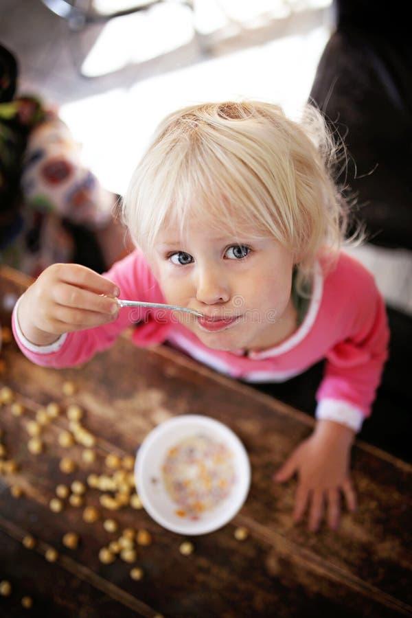 吃早餐谷物的逗人喜爱的小孩女孩在一个晴朗的早晨 免版税图库摄影
