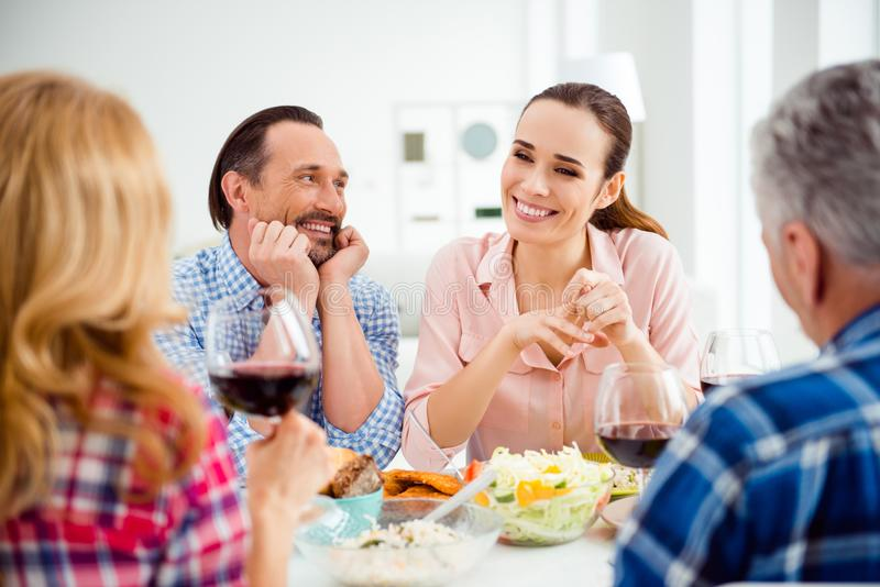 吃时髦,快乐,有吸引力的夫妇与亲戚的晚餐 免版税库存照片