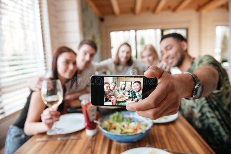 吃晚餐和采取与智能手机的小组朋友selfie 免版税库存照片