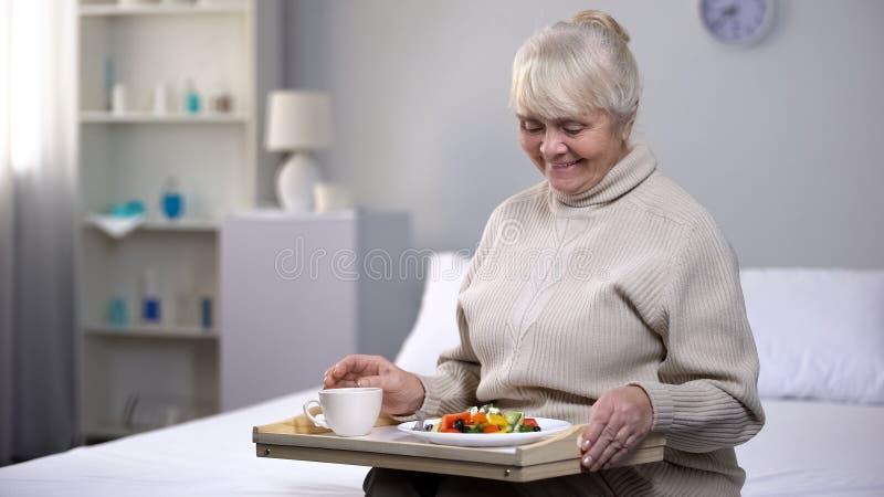 吃晚餐的微笑的老妇人在老人院,年迈的人民的社会保险 免版税图库摄影