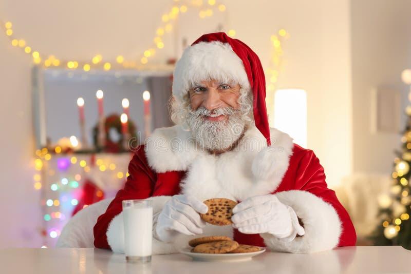 吃曲奇饼和饮用奶的圣诞老人项目在桌上在为圣诞节装饰的屋子里 免版税图库摄影