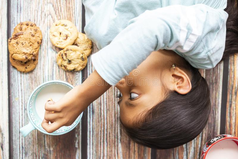 吃曲奇饼用牛奶的逗人喜爱的女孩 免版税库存图片