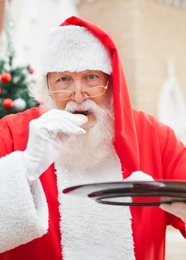 吃曲奇饼的圣诞老人户外 库存图片