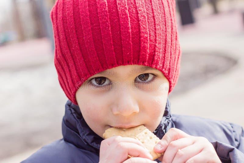 吃曲奇饼的婴孩户外 情感特写镜头画象 免版税库存照片