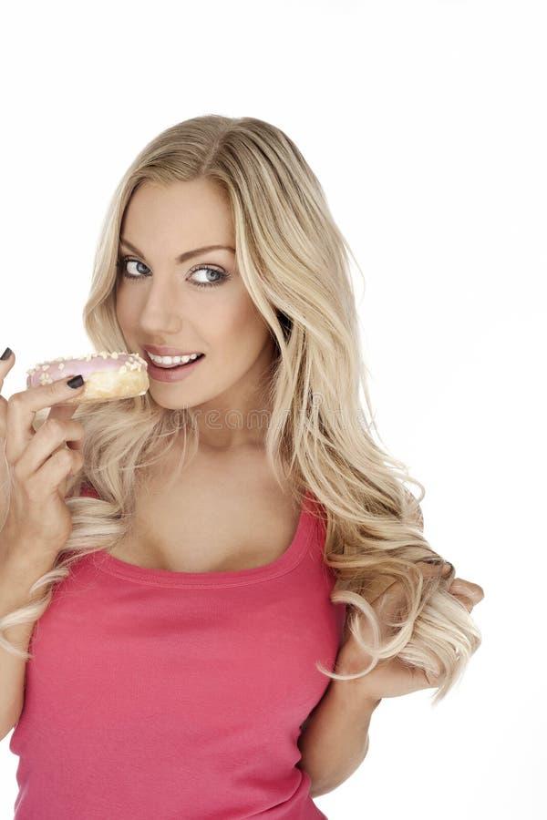 吃曲奇饼的迷人的金发碧眼的女人 免版税库存图片
