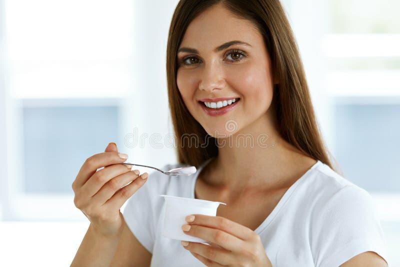 吃有机酸奶的美丽的妇女 健康饮食营养 免版税库存照片