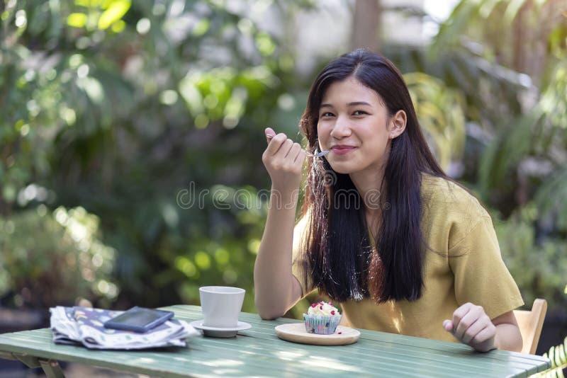吃杯形蛋糕用热的咖啡的年轻亚裔女孩在庭院里 免版税图库摄影