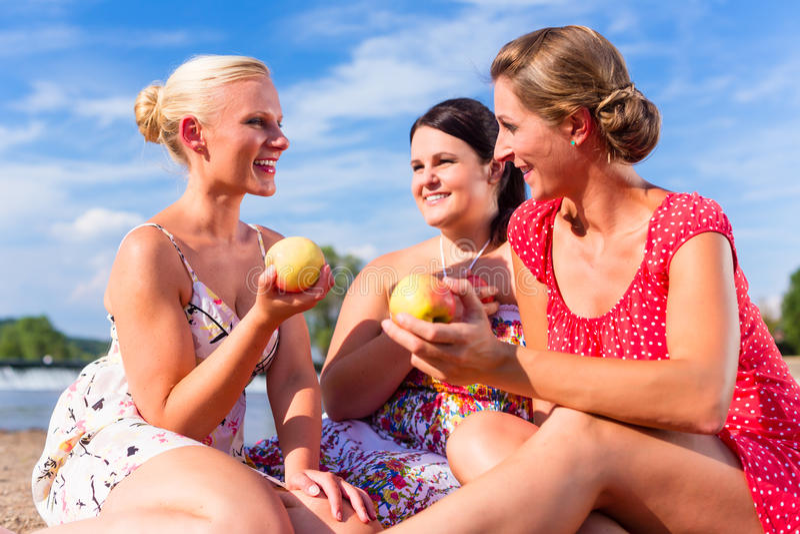 吃果子的妇女在河海滩野餐 免版税图库摄影