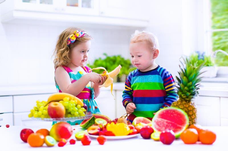 吃果子的孩子在一个白色厨房里 免版税库存照片