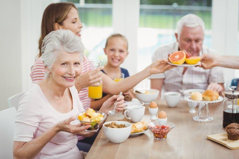 吃果子的愉快的多代的家庭在早餐期间 免版税库存图片