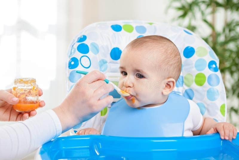 吃果子饲料的逗人喜爱的饥饿的婴孩 库存图片
