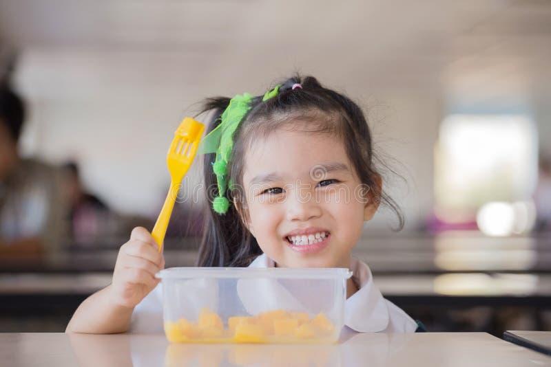 吃果子,许多的孩子在桌上的新鲜水果在前面在学校以后 免版税库存图片