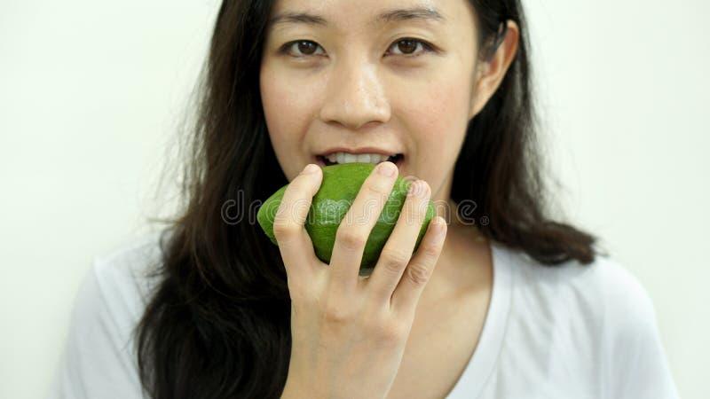 吃果子,鲕梨的亚裔女孩 清洗食物,健康和重量 库存照片