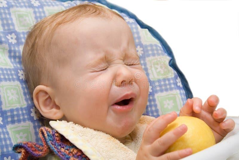 吃查出的柠檬的婴孩背景 免版税图库摄影