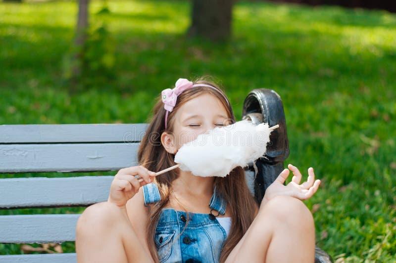 吃棉花糖的小女孩坐一条长凳在公园夏天 图库摄影