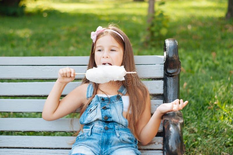 吃棉花糖的小女孩坐一条长凳在公园夏天 免版税库存图片